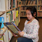 Student reading book next to library shelf